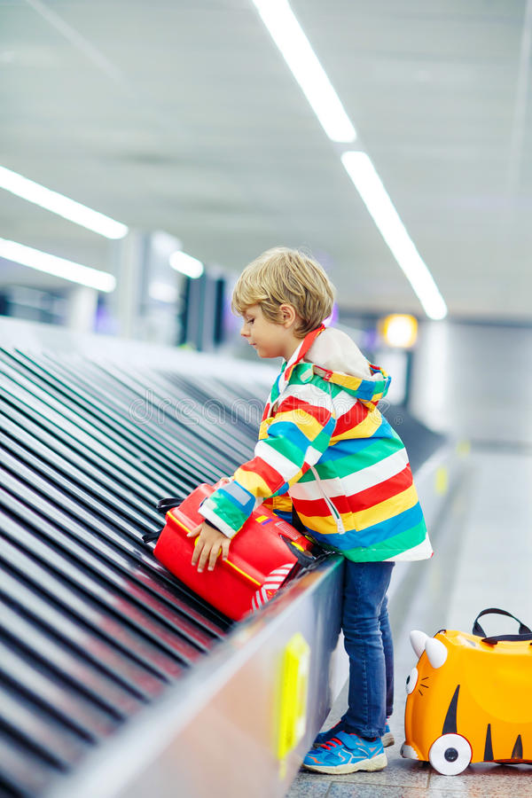 Little tired kid boy at the airport, traveling. Cute little tired kid boy at the airport, traveling. Upset child waiting with kids suitcase on baggage carousel stock photo