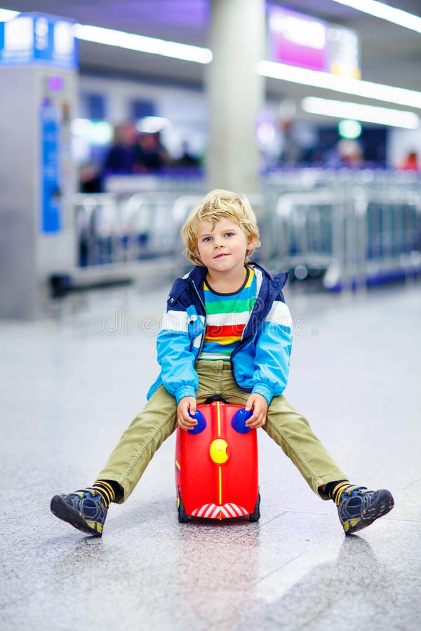 Little tired kid boy at the airport, traveling. Cute little tired kid boy at the airport, traveling. Upset child waiting with kids suitcase. Canceled flight due stock photography
