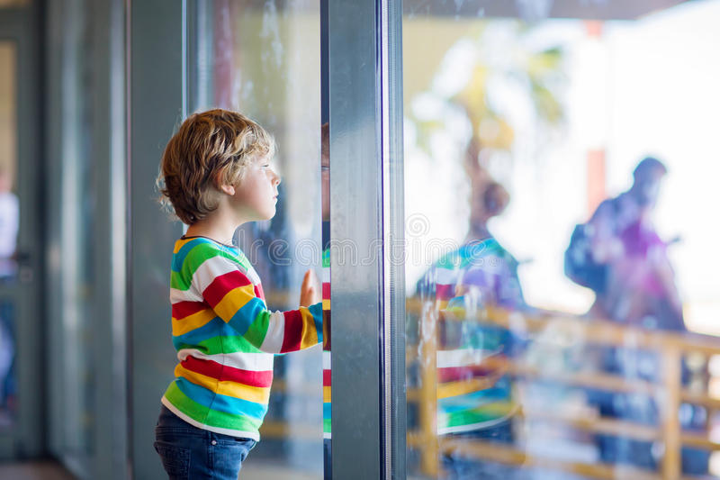 Little tired kid boy at the airport, traveling. Cute little tired kid boy at the airport, traveling. Upset child waiting near window and looking at plane royalty free stock images