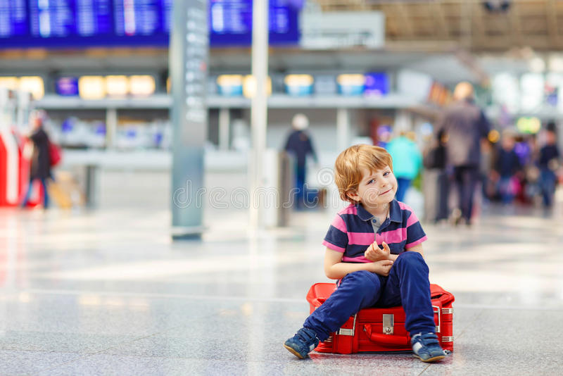 Little tired kid boy at the airport, traveling. Cute little tired kid boy at the airport, traveling. Upset child waiting and sitting on big suitcase. Canceled royalty free stock photo