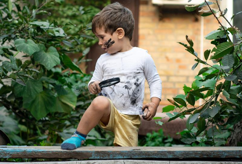 Little toddler boy with dirty face and dirty clothes looking through a magnifying glass on nature. stock photo