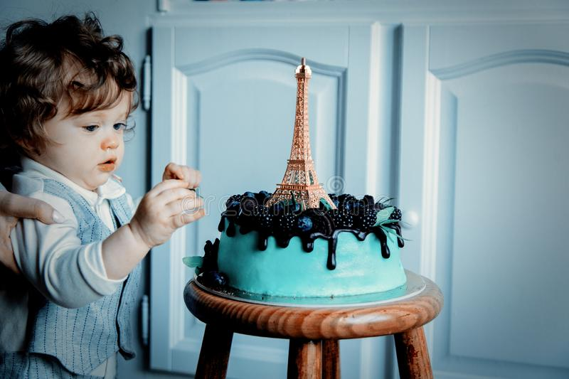 Little toddler boy with his first cake on Birthday. Cake is with cream and Eiffel tower on it stock image