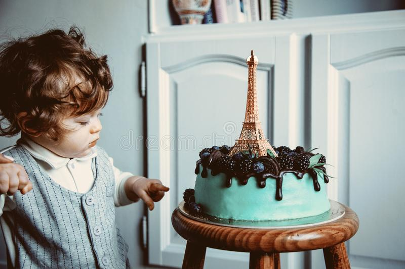 Little toddler boy with his first cake on Birthday. Cake is with cream and Eiffel tower on it royalty free stock photos