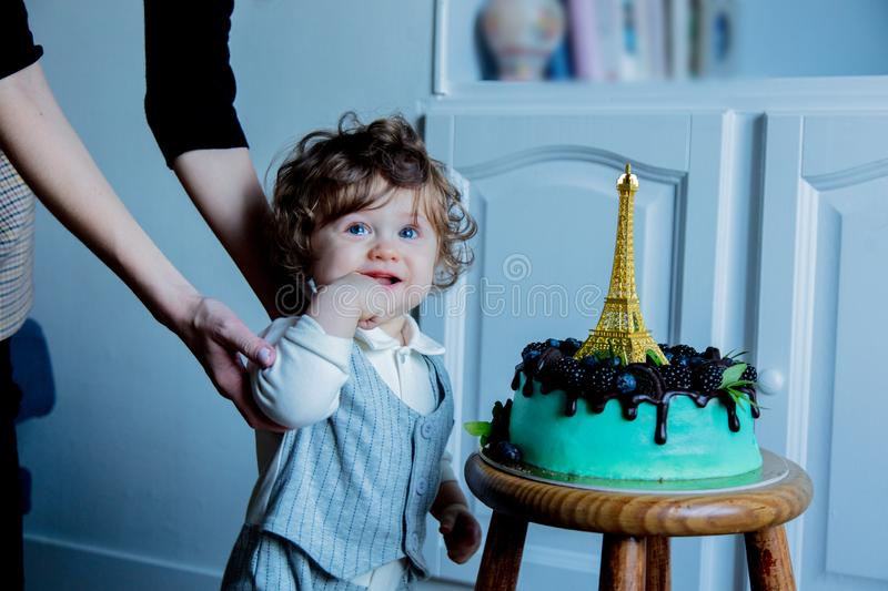 Little toddler boy with his first cake on Birthday. Cake is with cream and Eiffel tower on it stock images