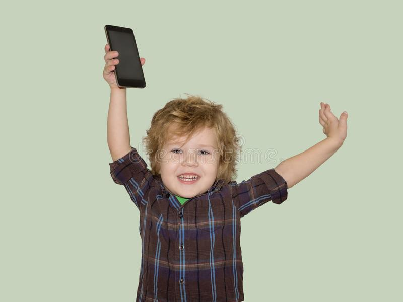 A little toddler boy picks up a smartphone gadget above his head. A satisfied child is happy that he was allowed to play phones with his smartphone royalty free stock photos
