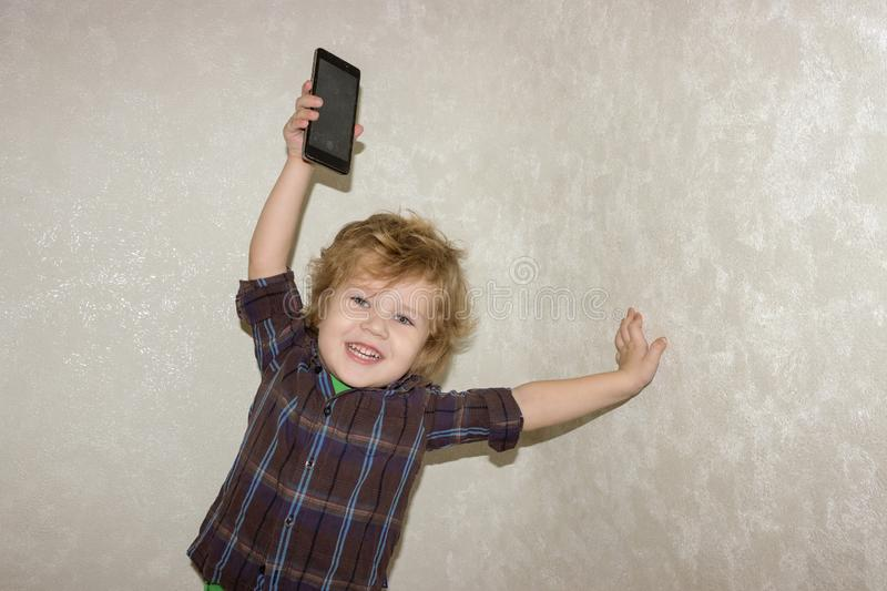 A little toddler boy picks up a smartphone gadget above his head. A satisfied child is happy that he was allowed to play phones with his smartphone royalty free stock images