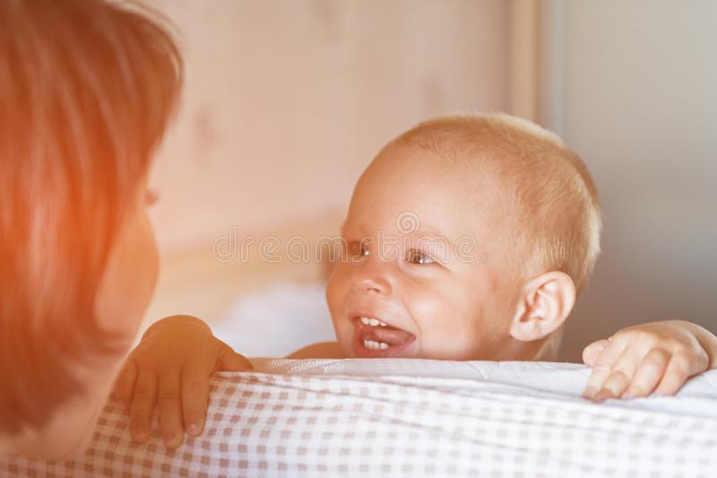 Little toddler boy playing on the bed. Cute kid smiling and hiding under cover. Palyful and mischievous eyes. Hide-and-seek. stock photos
