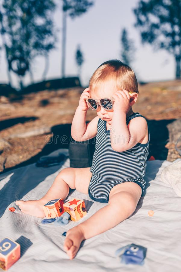 Little toddler boy putting on sunglasses on a blanket at the beach royalty free stock photography