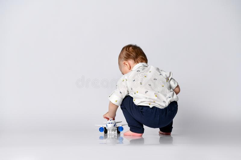 Little toddler boy sits back on a light wall background in an empty room with a toy airplane royalty free stock photos