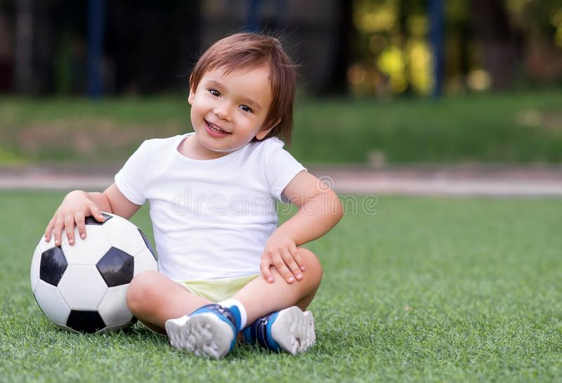 Little toddler boy sitting with legs crossed on football field in summer day with soccer ball. Happy active child. Little toddler boy sitting with legs crossed royalty free stock photography