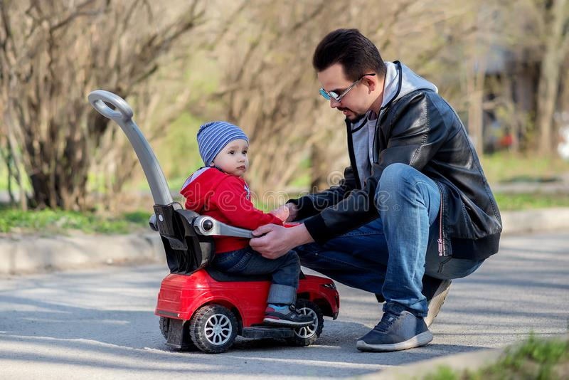 Little toddler boy sitting on red push car and listening to his father explaining him traffic law and safety rules. Father and son royalty free stock images