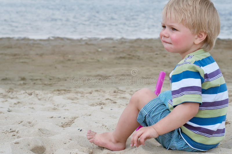 Little toddler boy sitting on sand beach stock photo
