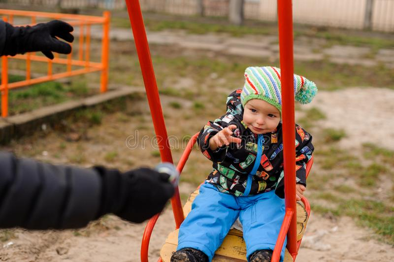 Little toddler boy sitting in a swing stock image