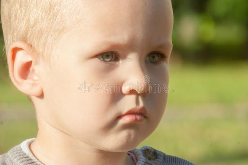 A little toddler boy is upset, sad, focused and serious. The child is offended. royalty free stock photography