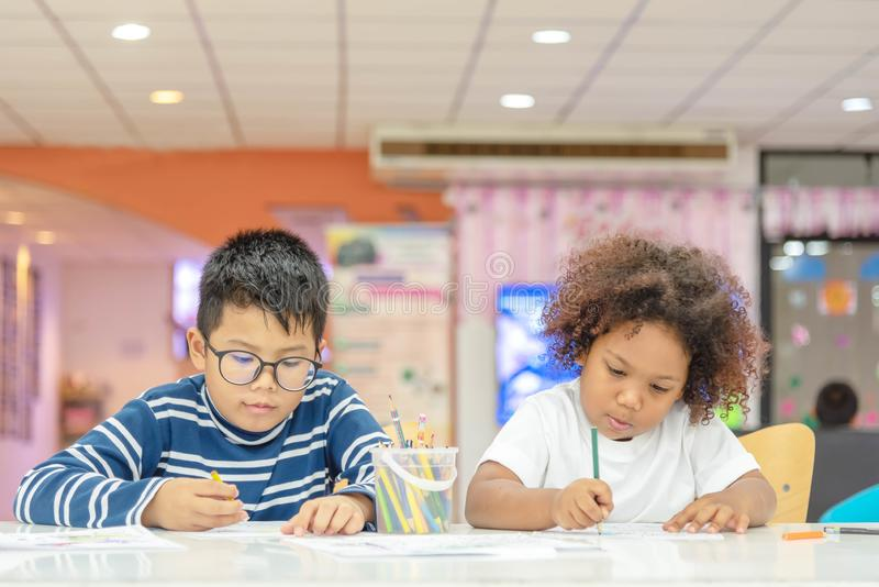 Little toddler girl and boy concentrate drawing together. Asian boy and Mix African girl learn and play together in the pre- royalty free stock photo