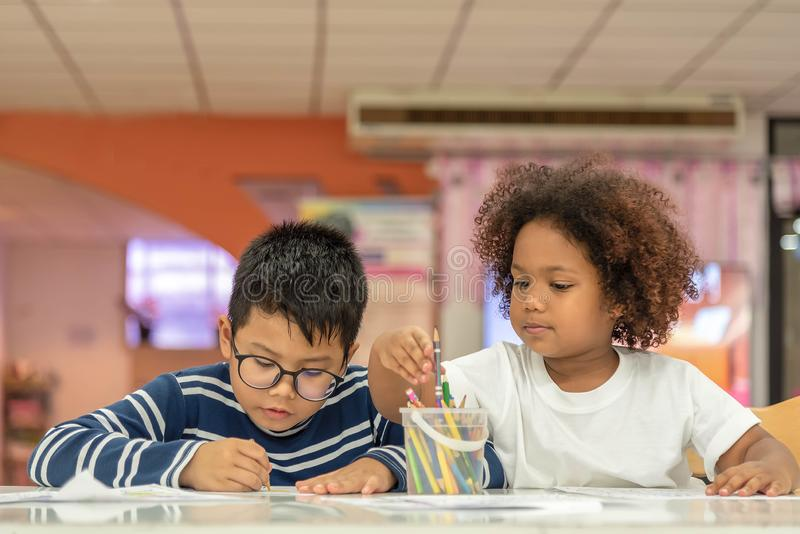 Little toddler girl and boy drawing together.  Asian boy and Mix African girl learn and play together in the pre-school class. royalty free stock photography