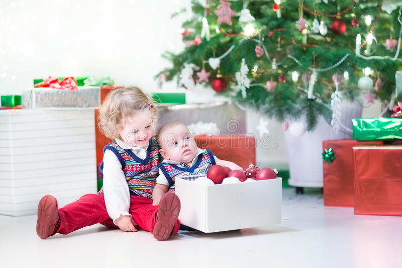 Little toddler girl and her newborn brother decorating Christmas tree stock image
