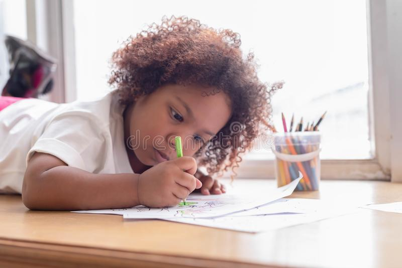 Little toddler girl laying down concentrate on drawing. Mix African girl learn and play in the pre-school class. Children enjoy royalty free stock image