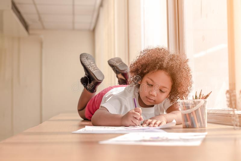 Little toddler girl laying down concentrate on drawing.  Mix African girl learn and play in the pre-school class. Children enjoy royalty free stock photo