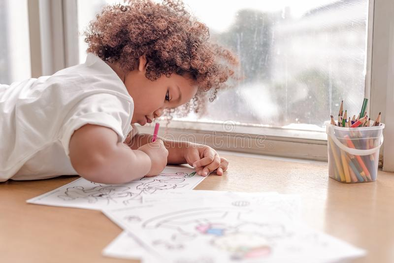 Little toddler girl laying down concentrate on drawing.  Mix African girl learn and play in the pre-school class. Children enjoy royalty free stock photos