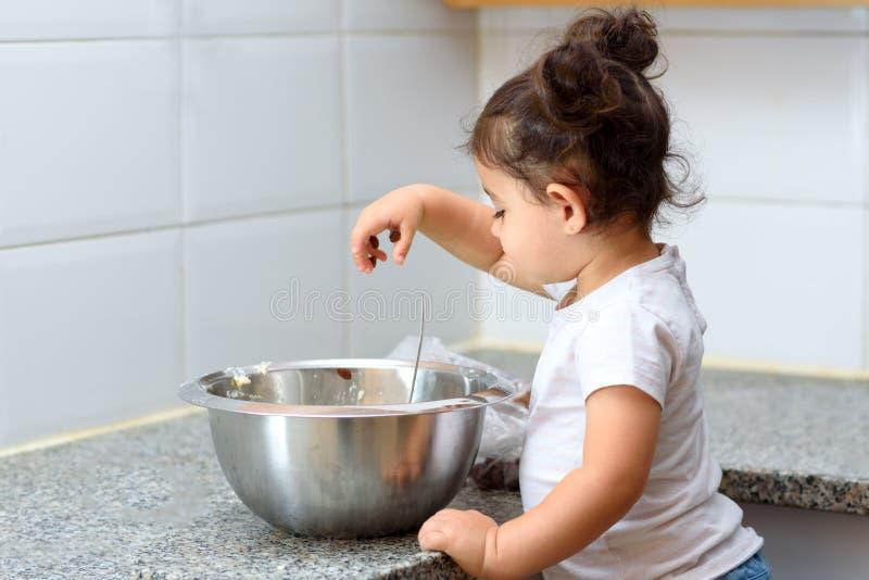 Little toddler girl making cake bakery in kitchen. royalty free stock photo