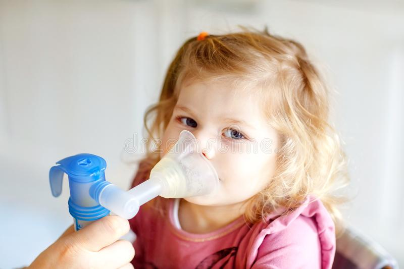 Little toddler girl making inhalation with nebulizer at home. Father or mother helping and holding the device. Child royalty free stock image