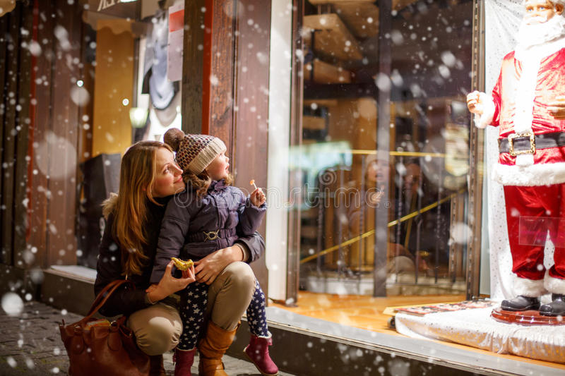 Little toddler girl with mother on Christmas. Market. Funny happy kid making window shopping with Santa Claus. holidays, christmas, childhood and people concept royalty free stock photos