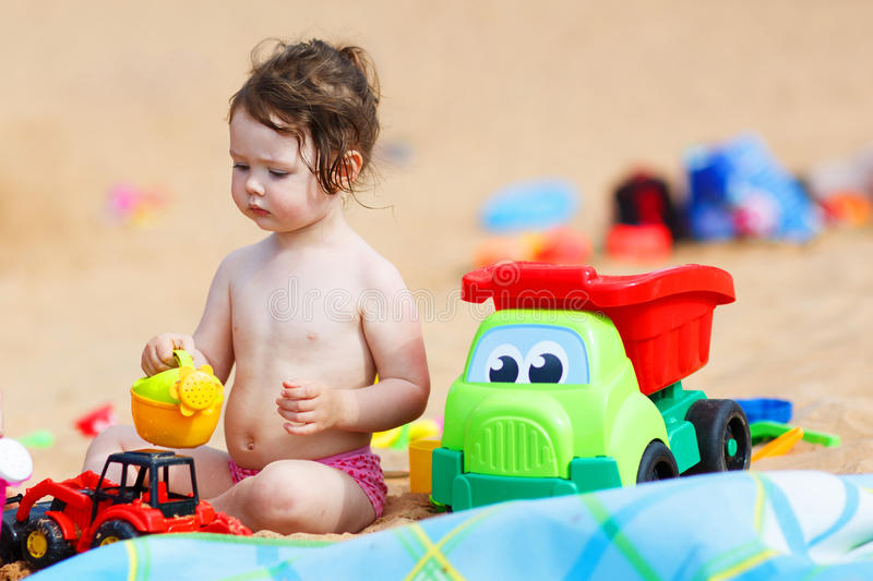 Beach Toys For Girls : Little toddler girl playing with sand toys on the beach