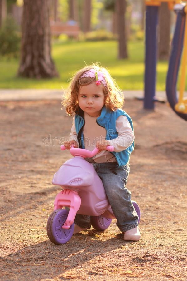 Little toddler girl riding a small pink bike in the sunlit park royalty free stock photo