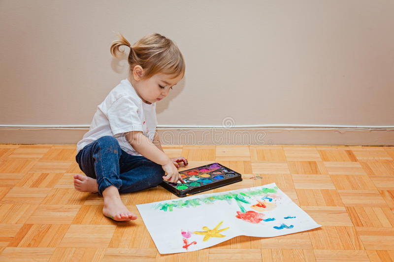 Little toddler girl trying to draw with her finger. Paints, paper, creative. stock photo