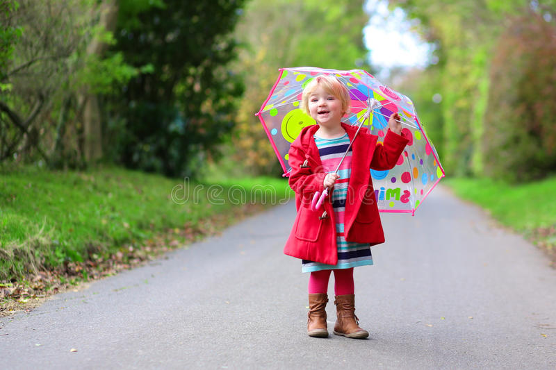 Little toddler girl walking with umbrella. Happy little child, adorable blonde curly toddler girl wearing red duffle coat and holding colorful umbrella walking stock photo