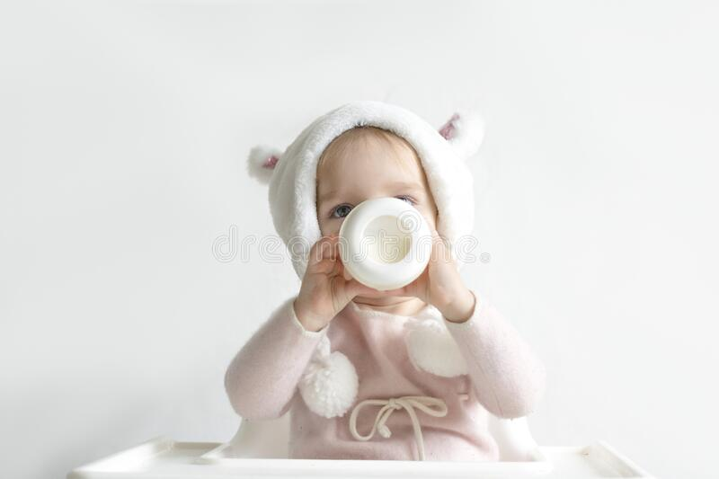 Little toddler girl in a warm fluffy hat drinks milk from a bottle while sitting. Half-length portrait. White gray stock image