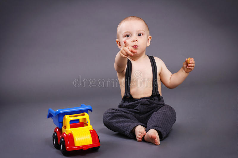 Little toddler playing with car and eating biscuit. Studio portrait stock image