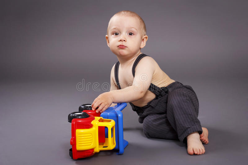 Little toddler playing with car. Studio portrait, gray background stock photography