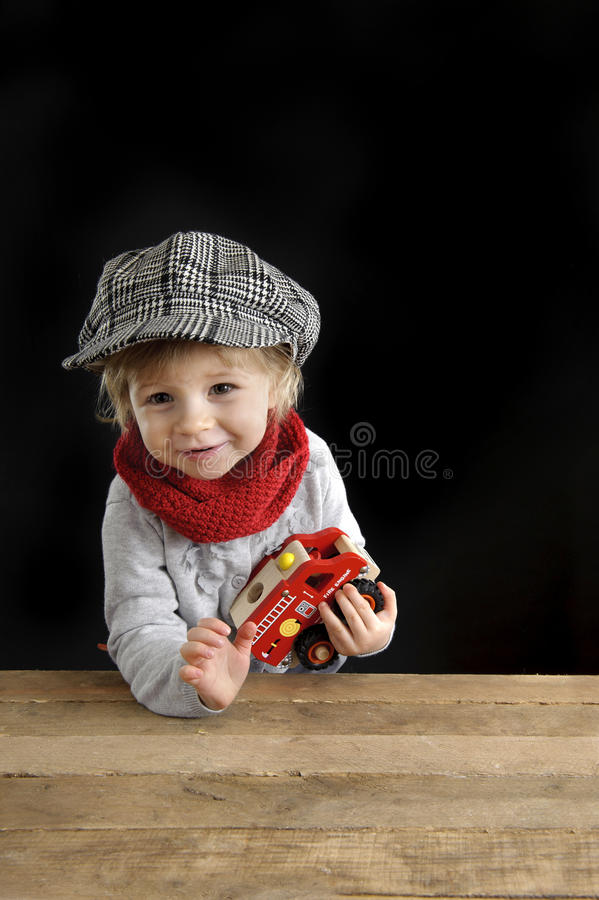 Little toddler playing with wooden cars. On black background stock photography