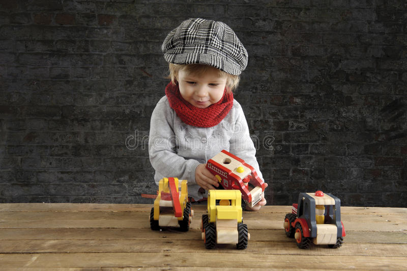 Little toddler playing with wooden cars. On black background stock image
