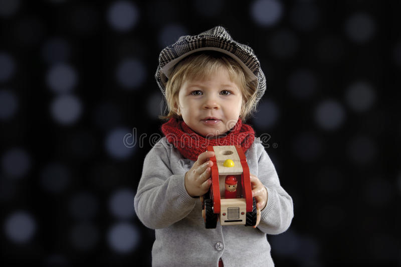 Little toddler playing with wooden cars. On black background royalty free stock images