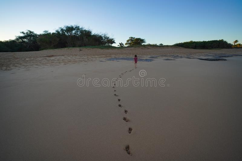 Little toddler running on the sandy beach leaving foot prints behind. stock photography