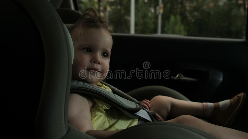 Little toddler smiles to camera sitting on child car seat royalty free stock photos