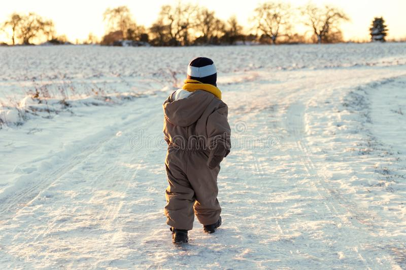 Little toddler walking outdoors in a snowy winter scene stock image