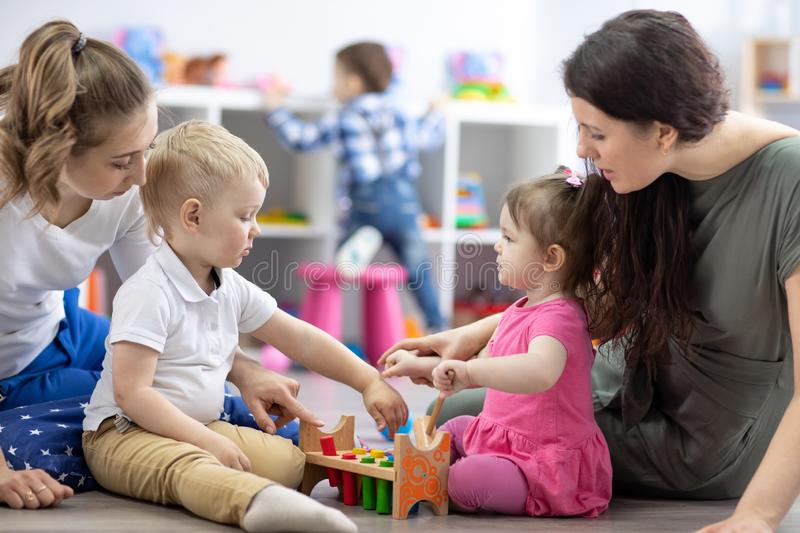 Little toddlers boy and girl with moms playing together in nursery room. Preschool children in day care centre stock images
