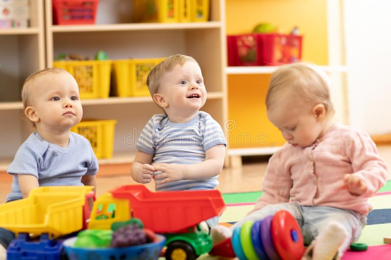 Little toddlers boys and a girl playing together in kindergarten room. Preschool children in day care centre. Little toddlers boys and a girl playing together in royalty free stock images