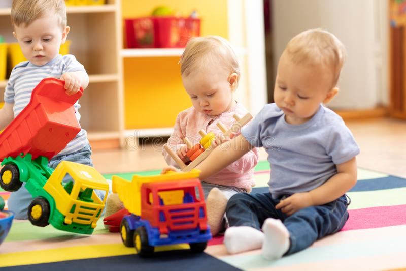 Little toddlers boys and a girl playing together in nursery room. Preschool children in day care centre royalty free stock image