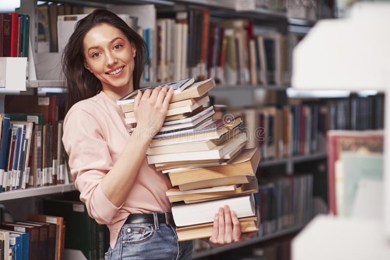 A little too much. Brunette girl in casual clothes having good time in the library full of books stock image