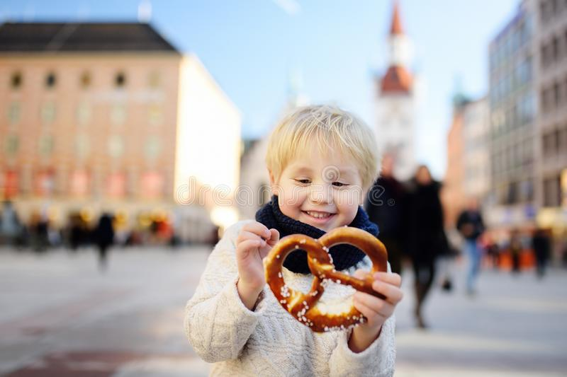 Little tourist holding traditional bavarian bread called pretzel on the town hall building background in Munich, Germany. Preschooler boy enjoy travel with his royalty free stock photo