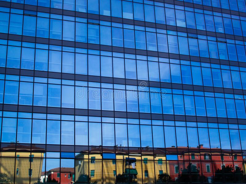 Little town colored houses reflecting on a big mirrored corporate building with blue sky as background royalty free stock photos