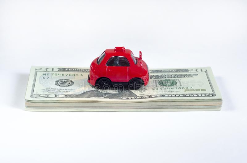 Little toy red car and a stack of money banknotes american dollars on a white isolated background. vehicle loan. royalty free stock photos