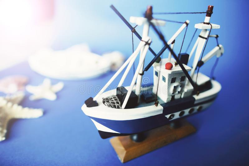 Little toy ship on a wooden stand with shells on a blue background. Copy space.  royalty free stock photography
