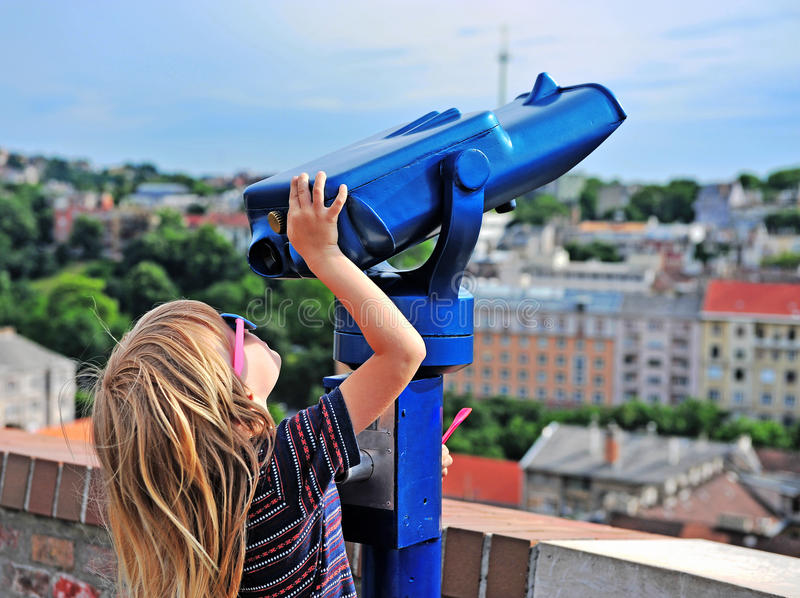 Little traveler trying to use binoculars. Little traveler trying to use coin-operated binoculars to see the city skyline royalty free stock image