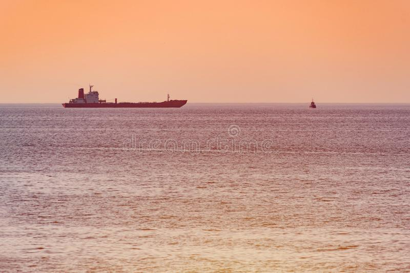 Little tugboat and big cargo ship. Beautiful sunset over sea. Breathtaking travel view, copy space royalty free stock photography